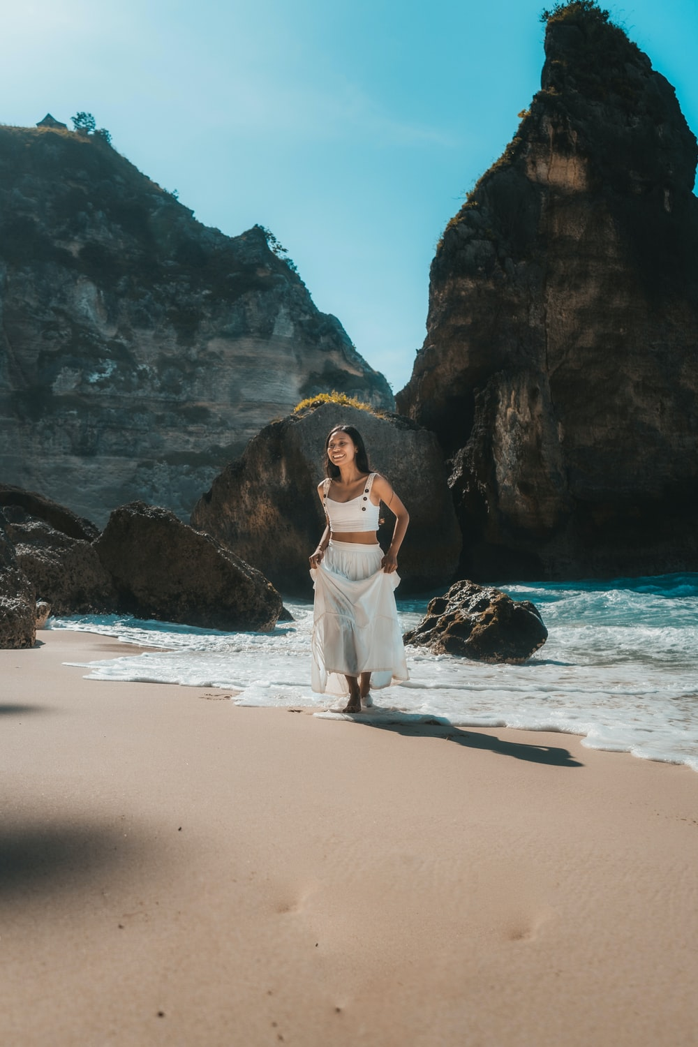 woman in white dress standing on beach during daytime