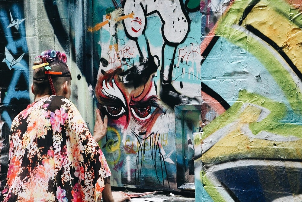 woman in red and white floral dress standing beside graffiti wall during daytime