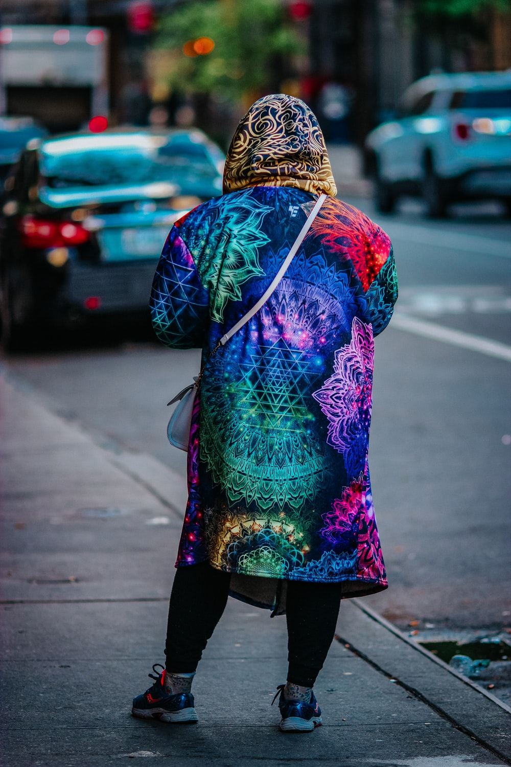 woman in purple and pink floral long sleeve dress standing on sidewalk during daytime