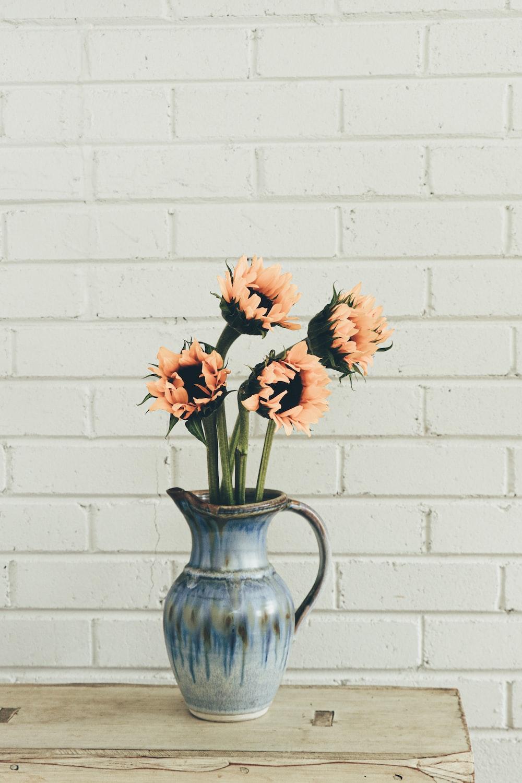 orange flowers in blue ceramic vase
