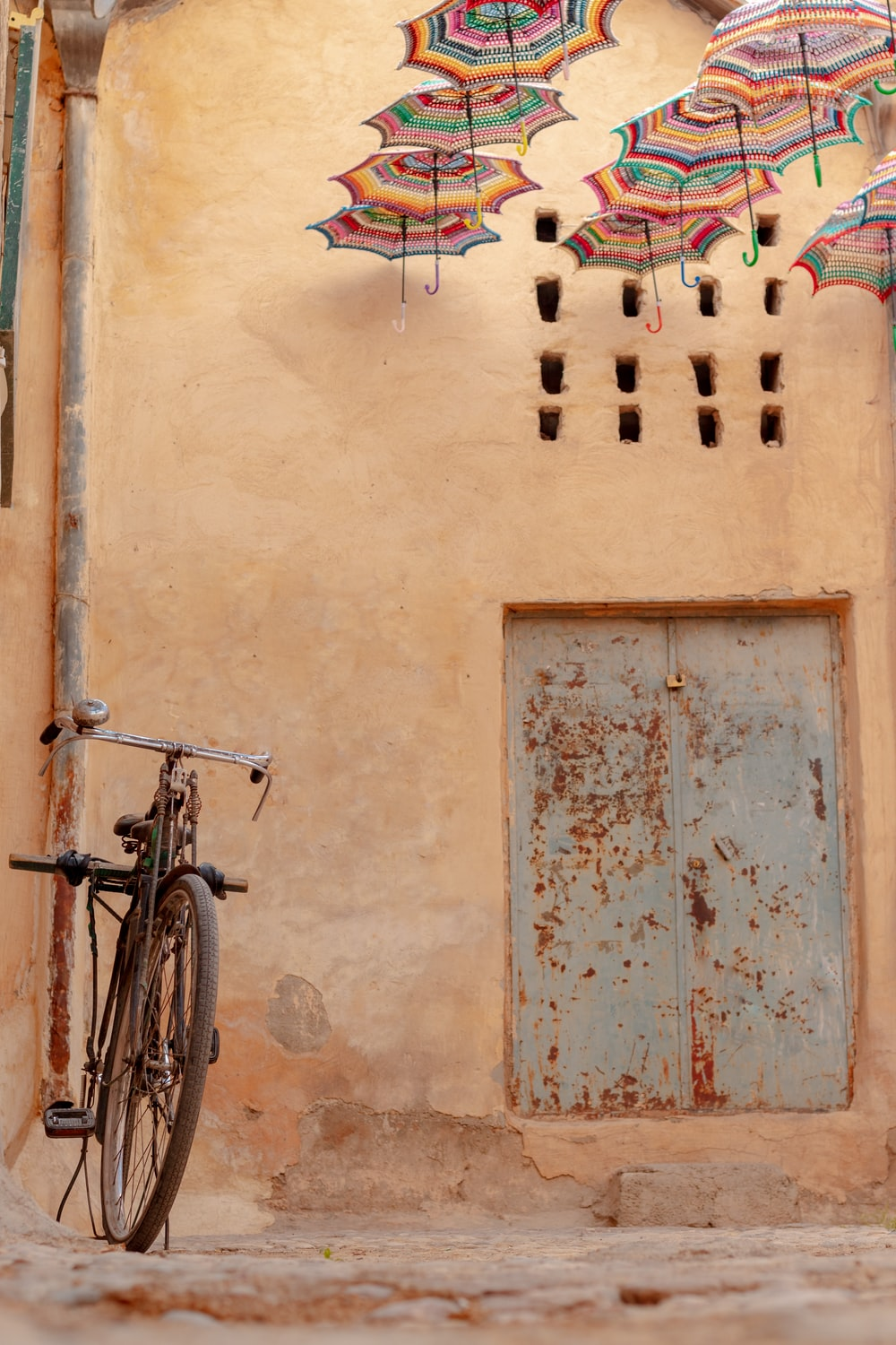 black bicycle leaning on brown concrete wall
