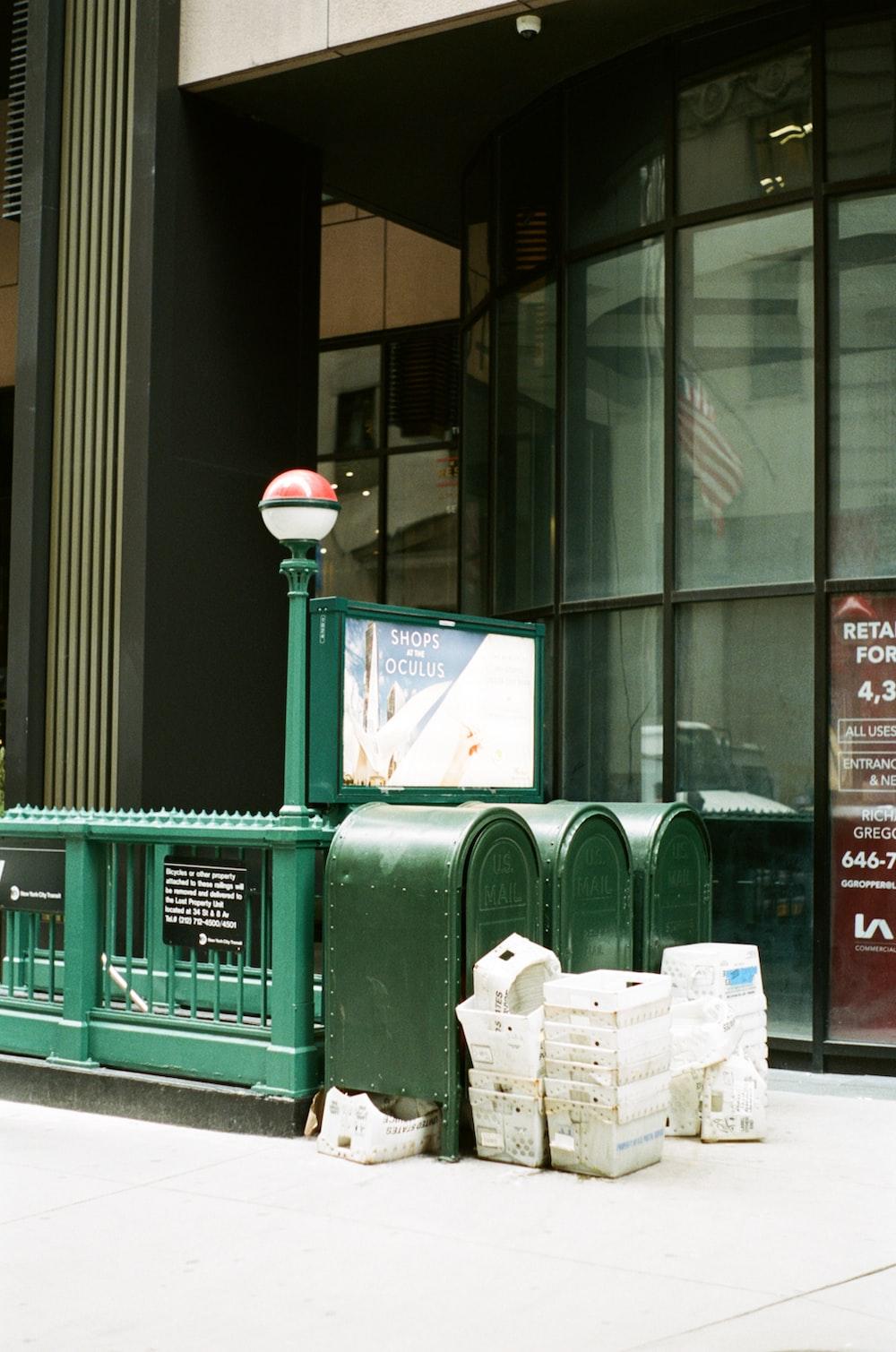green wooden trash bin near glass window