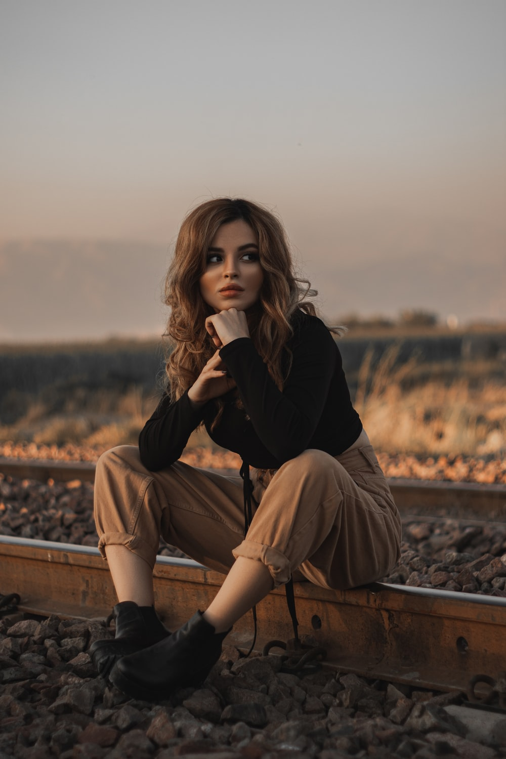 woman in black long sleeve shirt and brown pants sitting on brown wooden bench during daytime