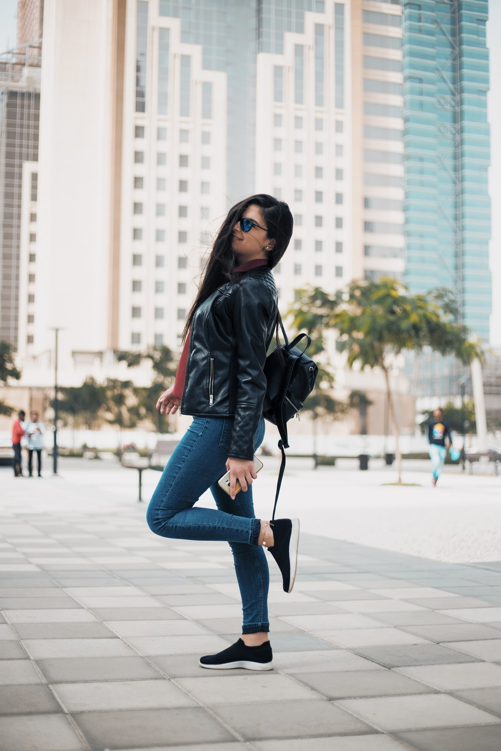 woman in black jacket and blue denim jeans standing on sidewalk during daytime