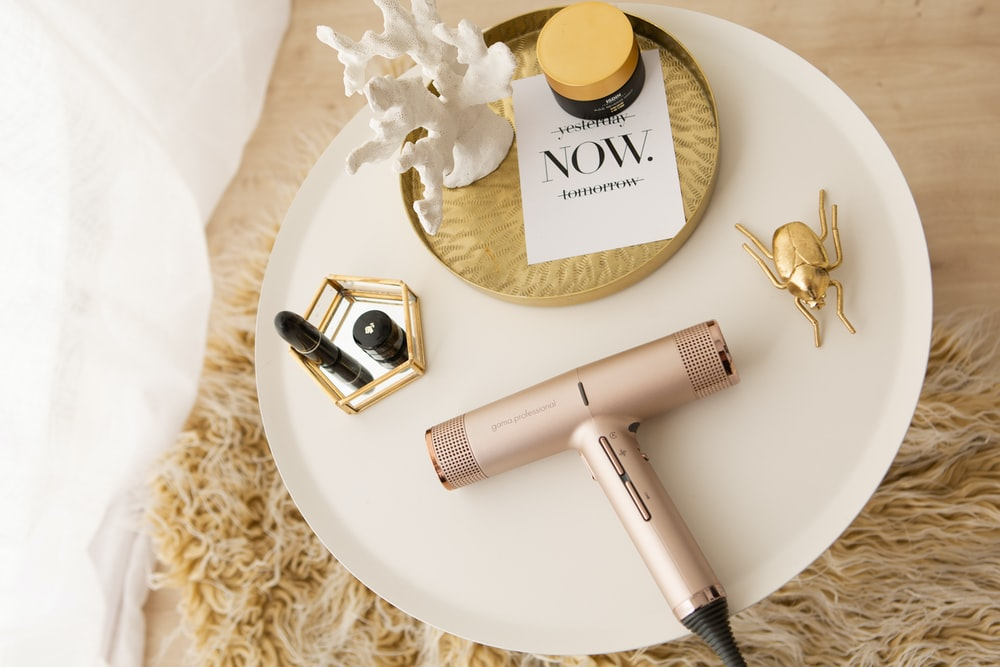 gold and silver hair dryer on white round table