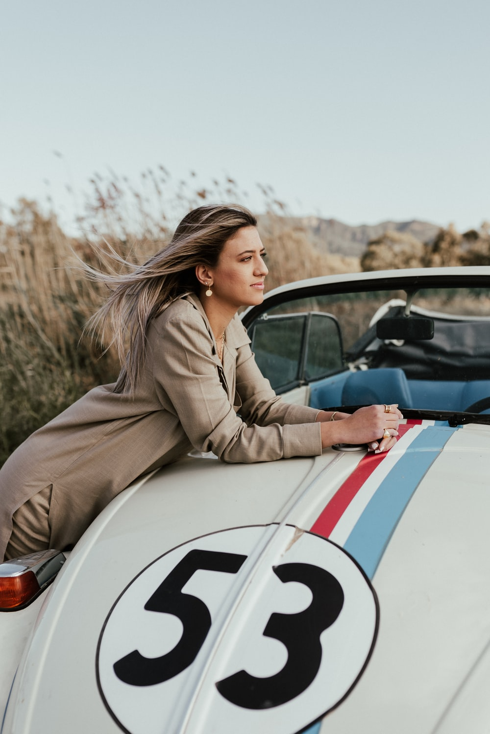 woman in brown coat sitting on white and blue car during daytime