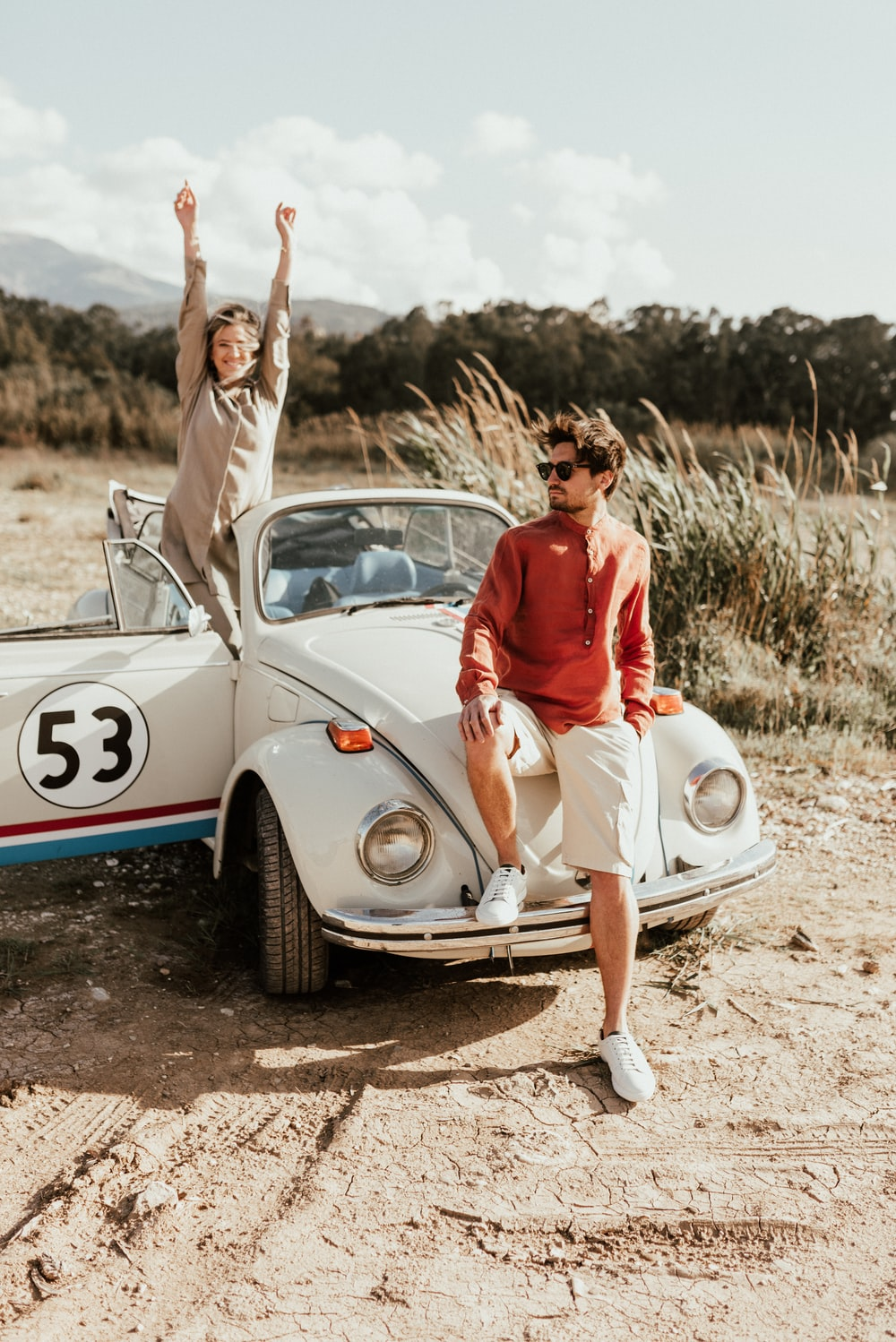 woman in red tank top and white pants sitting on white volkswagen beetle