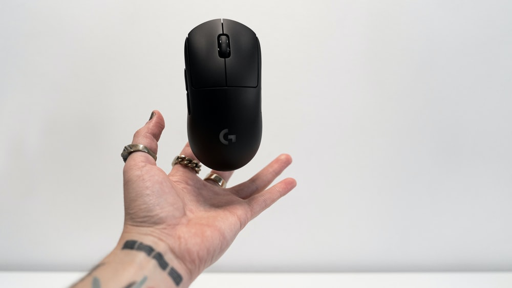 person holding black hp cordless computer mouse