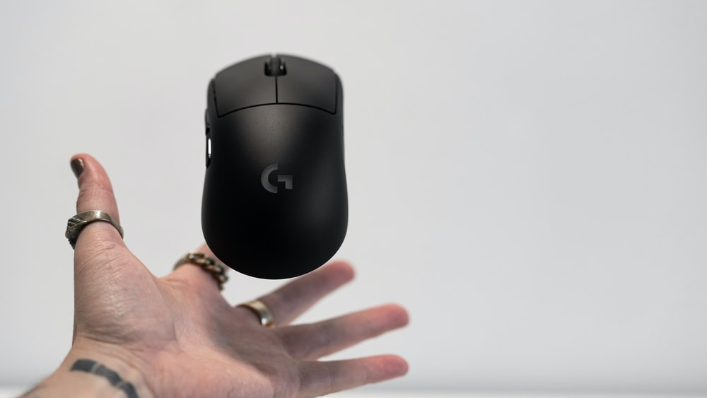 person holding black logitech cordless computer mouse