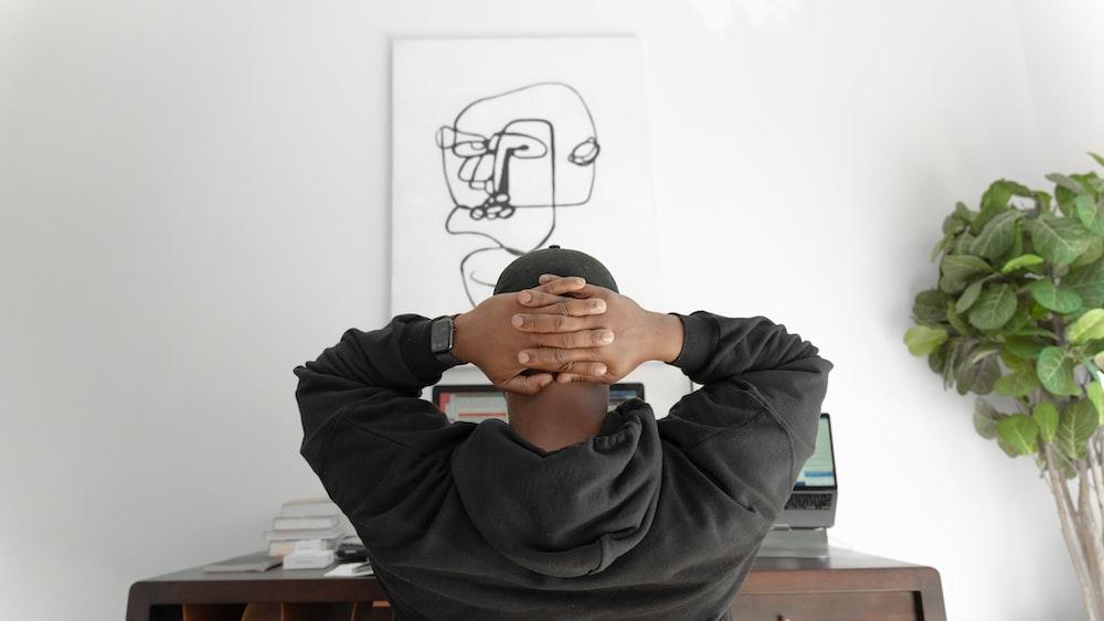 man in gray hoodie sitting on chair