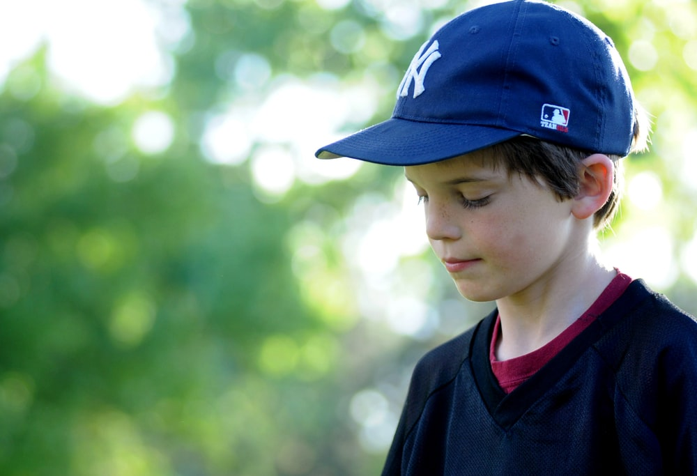boy in blue and red fitted cap and black v neck shirt