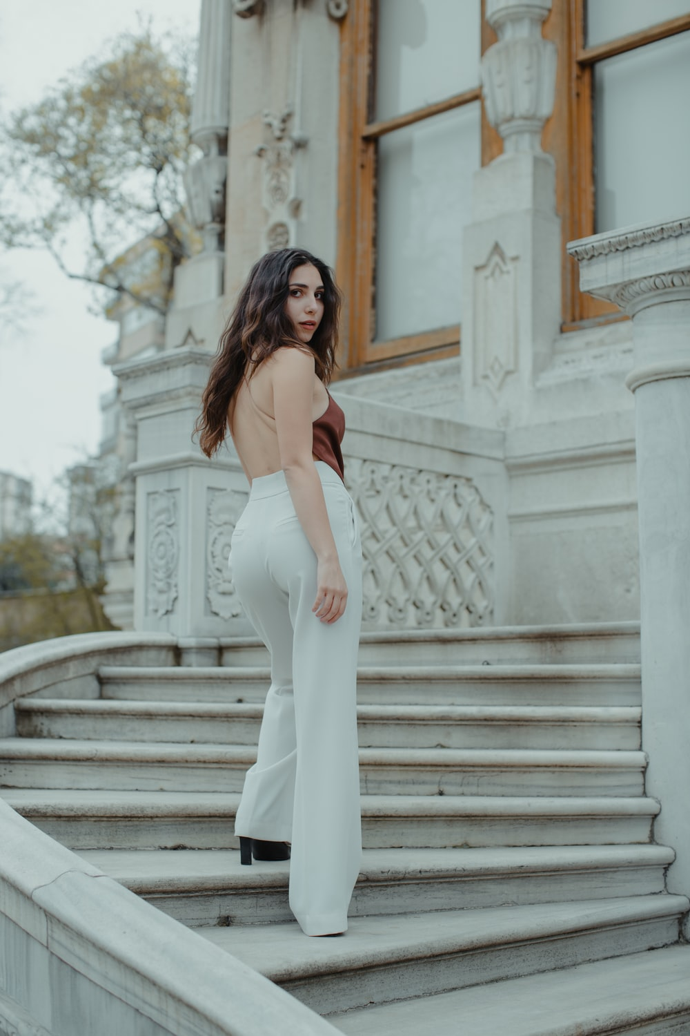 woman in white sleeveless dress standing on stairs during daytime