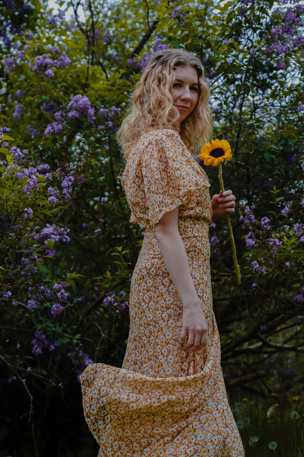 woman in yellow and white floral dress standing beside purple flowers