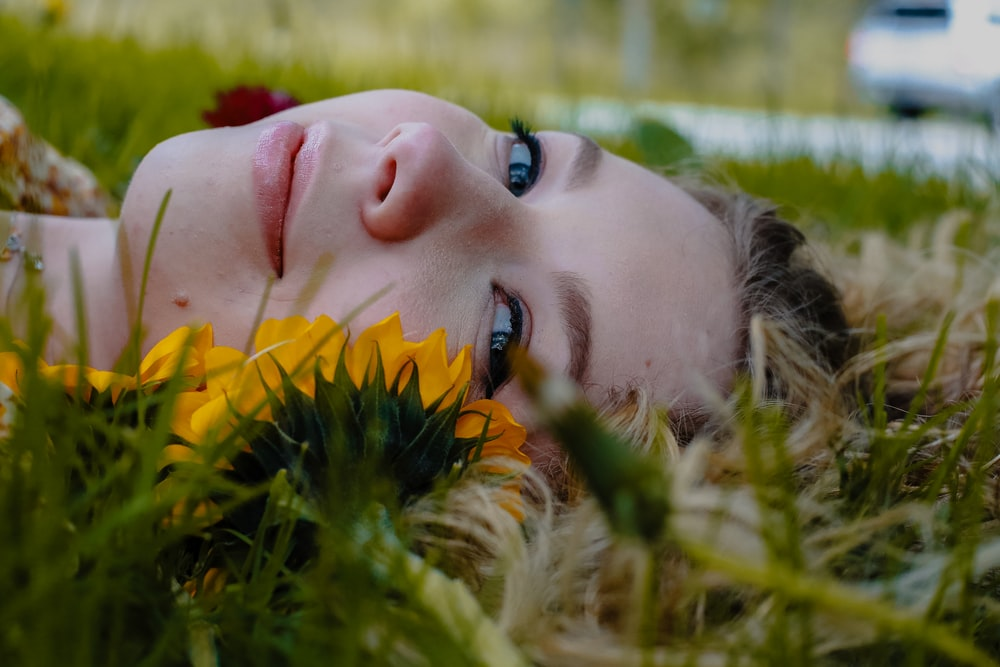 woman lying on green grass during daytime