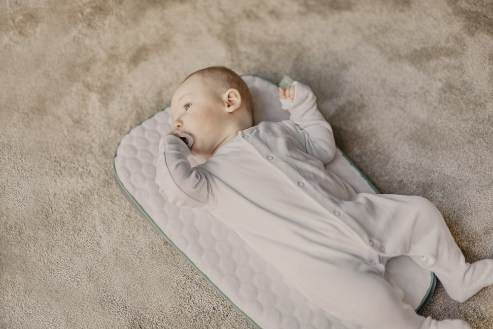 baby in white onesie lying on white and blue bed