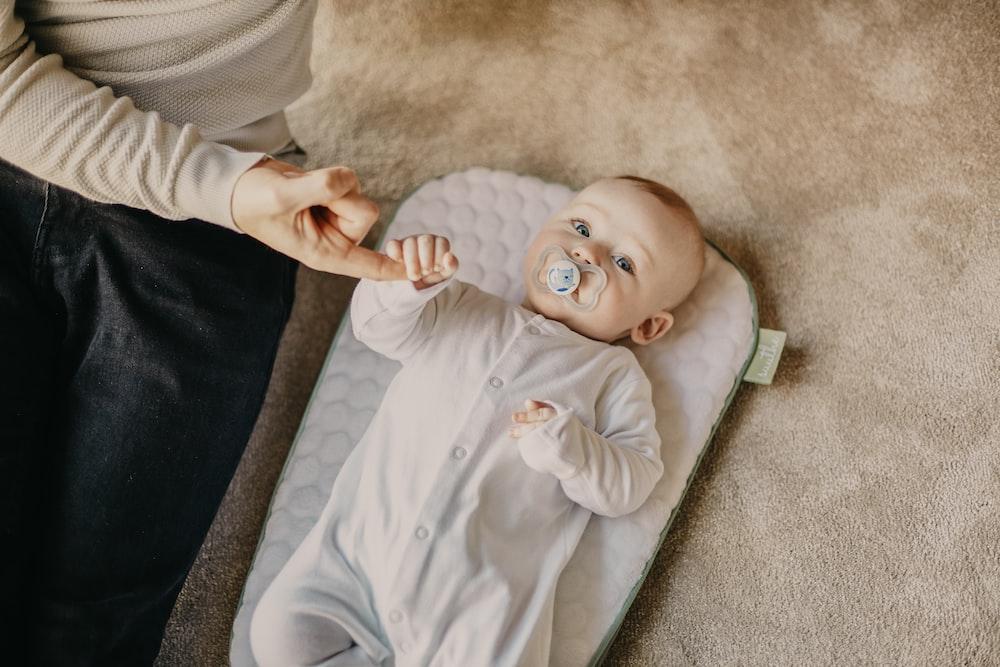 baby in white onesie lying on white textile