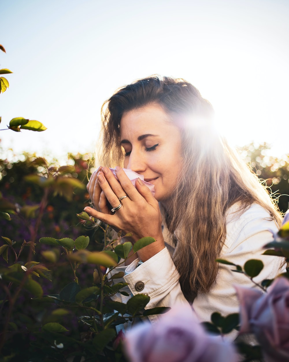 woman in white long sleeve shirt holding her face