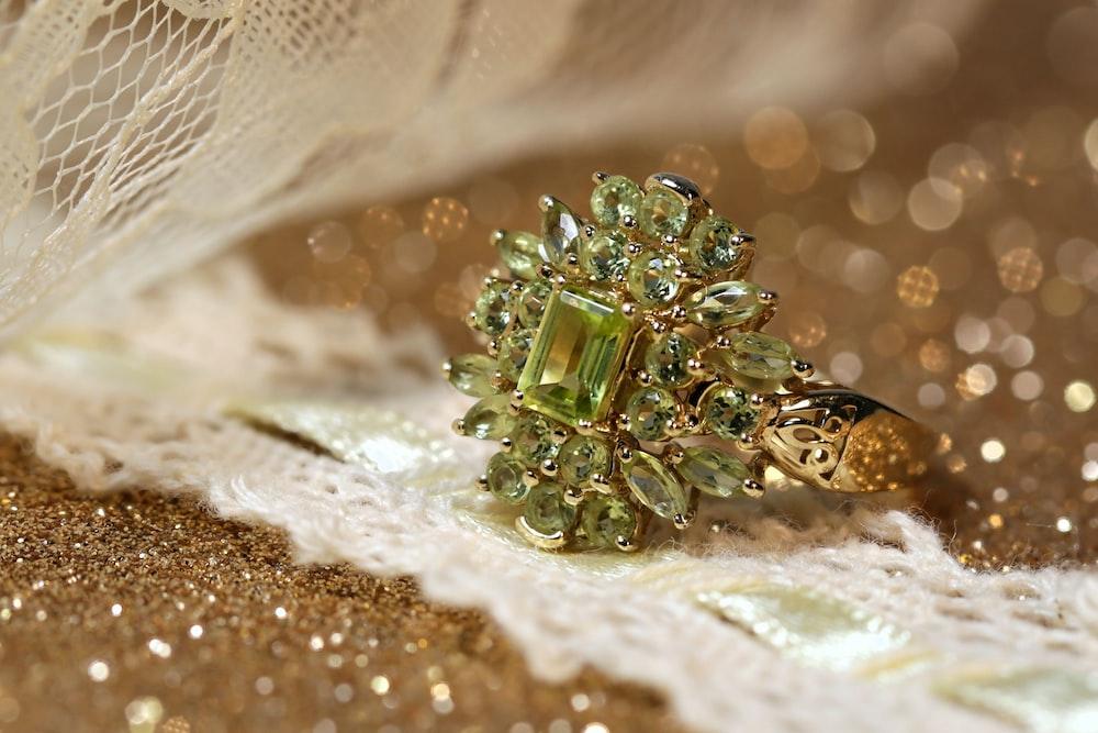 silver diamond studded ring on white textile
