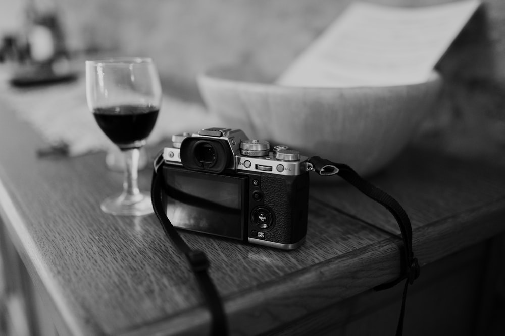 black and silver camera beside wine glass