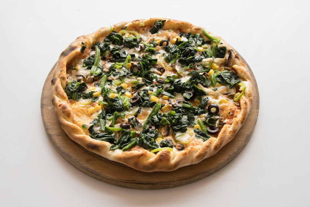 pizza with green leaves and cheese on brown wooden round plate