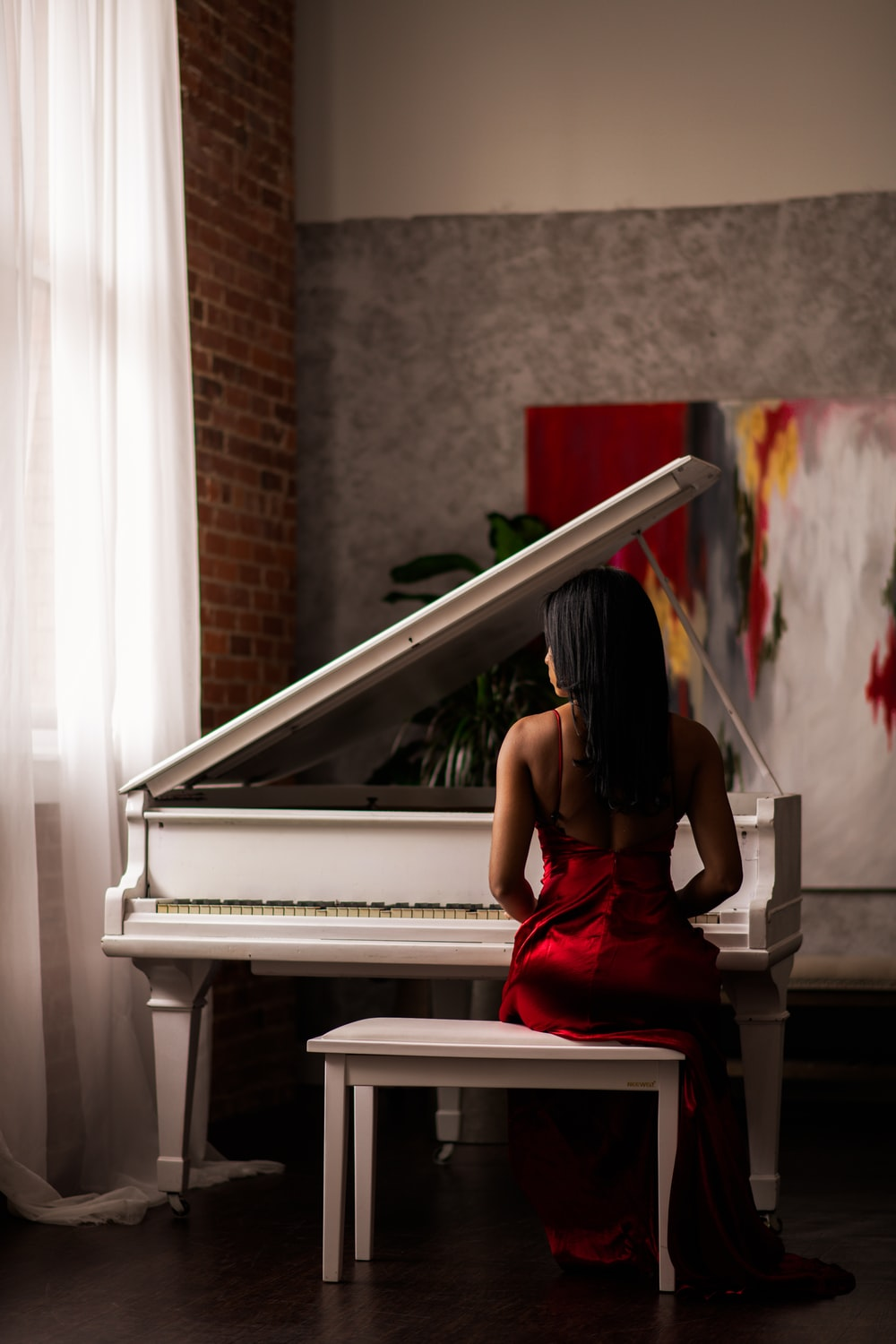 woman in red dress sitting on piano