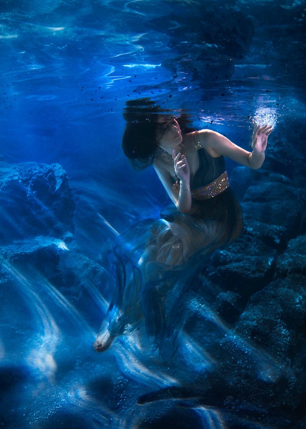 woman in black bikini swimming in water
