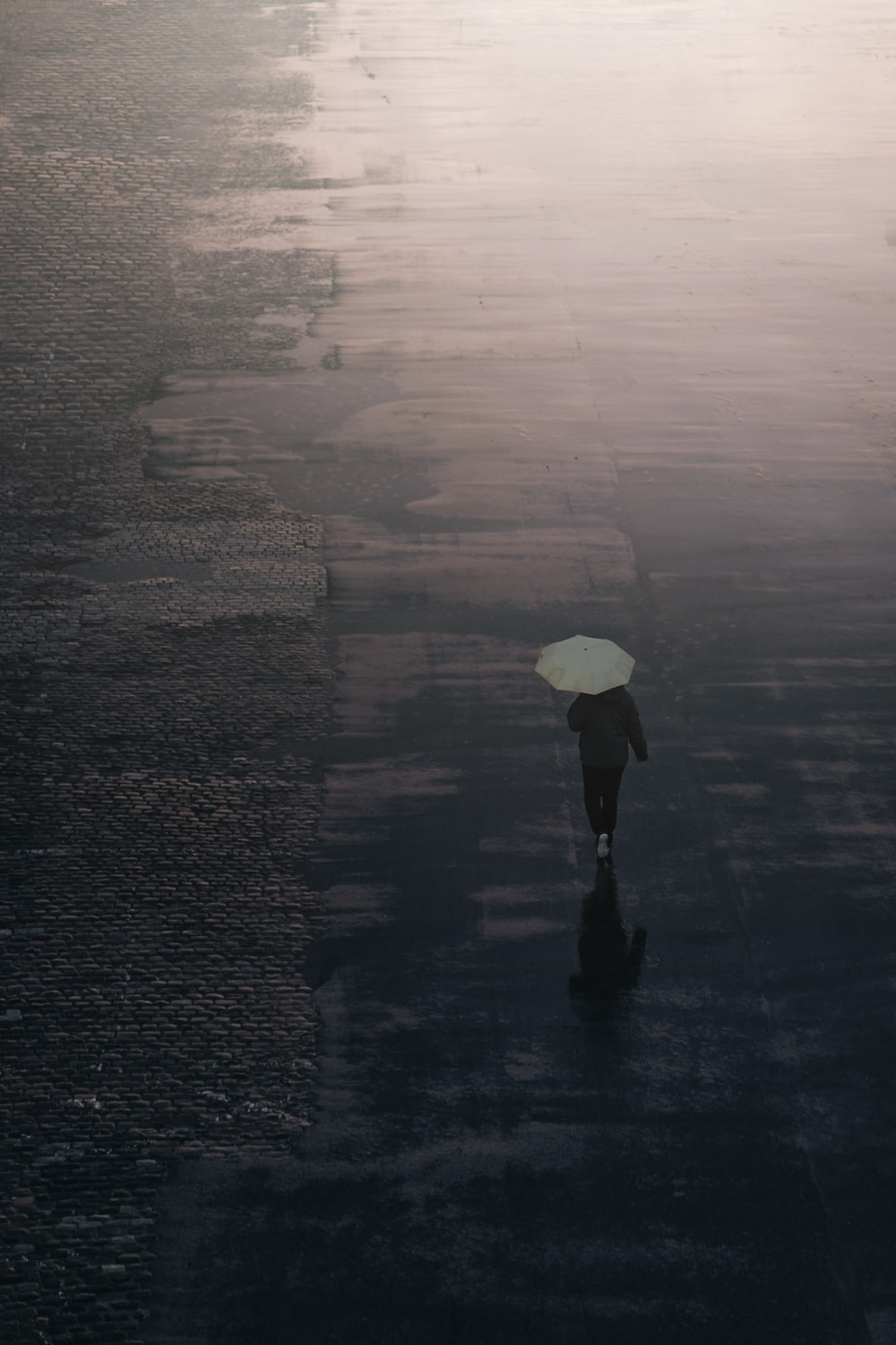 person in black jacket holding white umbrella walking on wet road during daytime