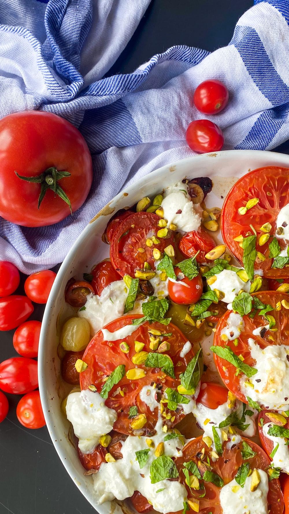 tomato and green vegetable salad on white ceramic bowl
