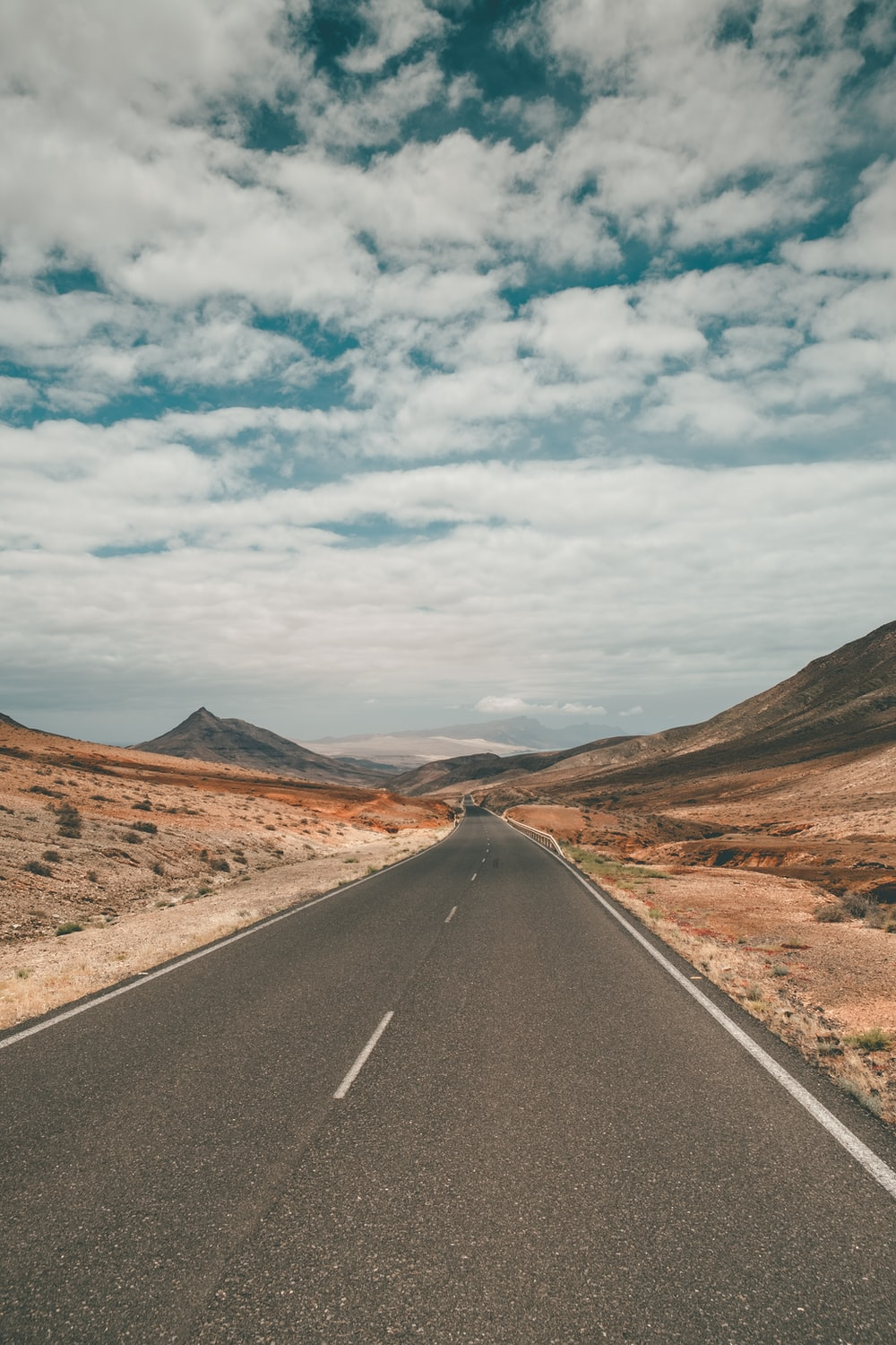 black asphalt road between brown mountains under white clouds and blue sky during daytime