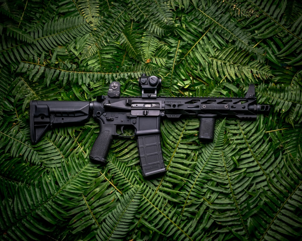 black rifle on green textile