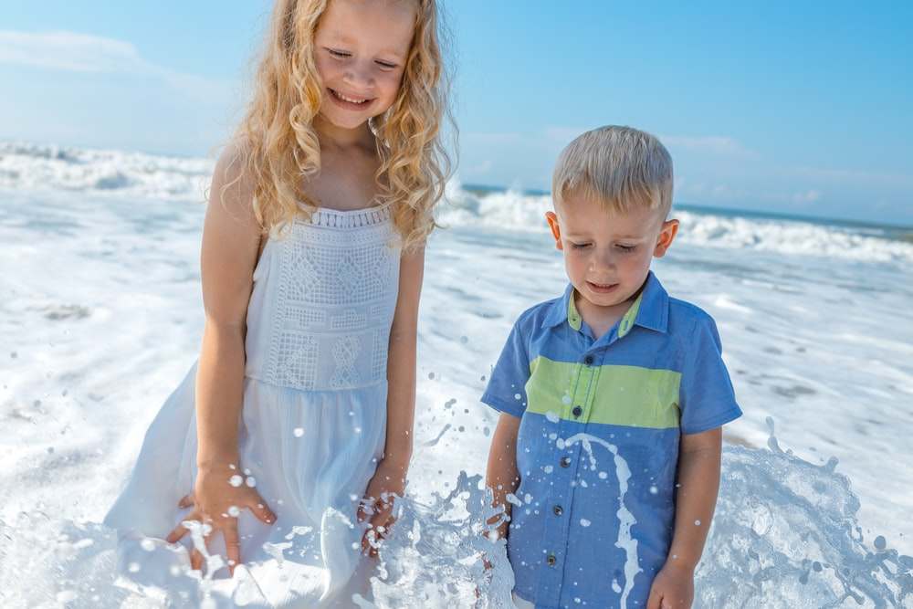 girl in white sleeveless dress standing beside boy in blue and green polo shirt during daytime