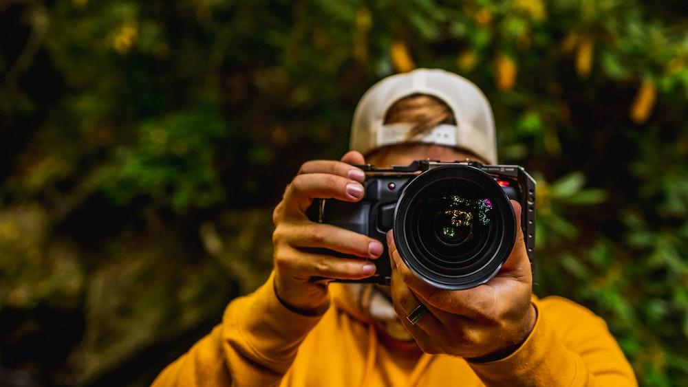 person in yellow long sleeve shirt holding black nikon dslr camera
