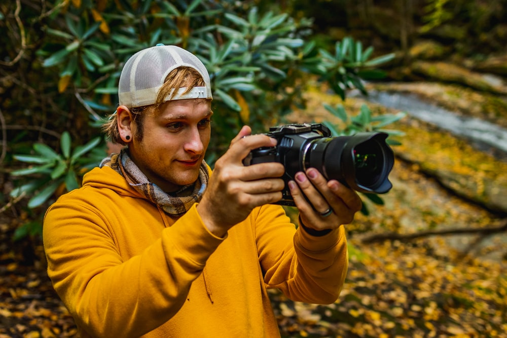 man in yellow jacket holding black dslr camera