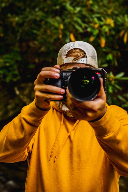 man in yellow hoodie taking photo using black dslr camera