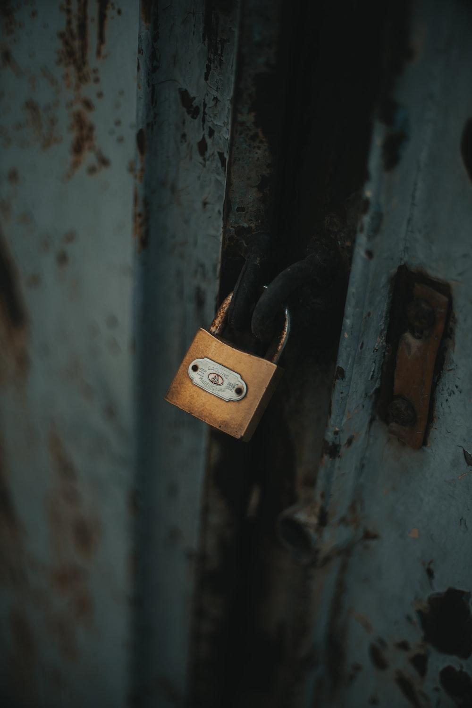 gold padlock on white wooden door
