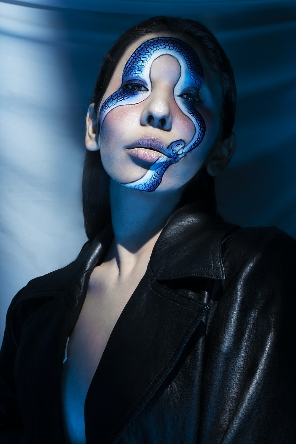 woman in black leather jacket with blue face paint