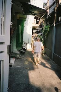 man in yellow t-shirt and brown pants walking on sidewalk during daytime