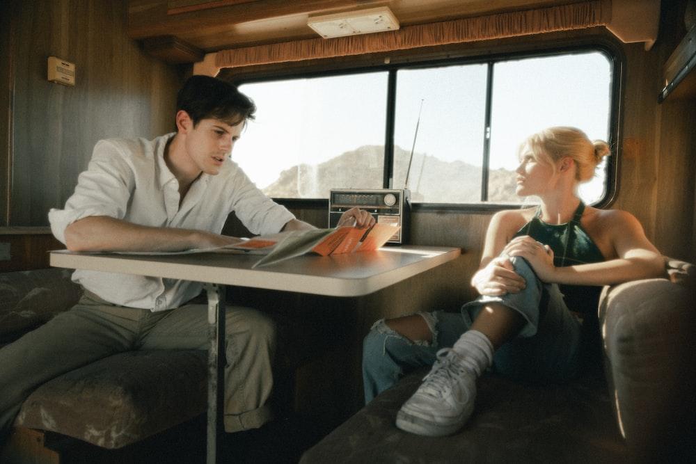 man in white dress shirt sitting beside woman in white long sleeve shirt