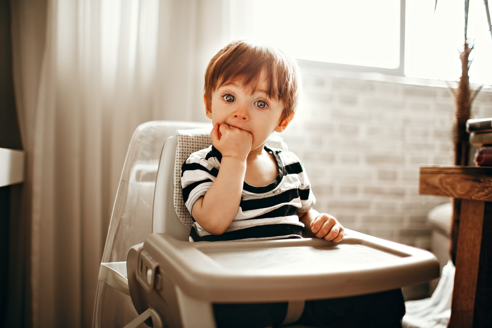 boy in black and white stripe shirt sitting on white plastic chair