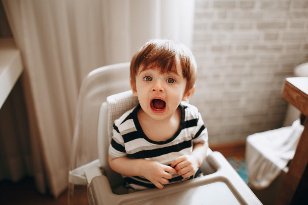 boy in black and white striped shirt sitting on white high chair