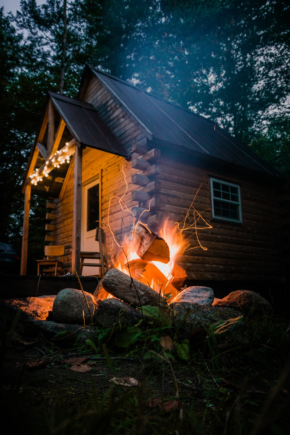 brown wooden house with fire during night time