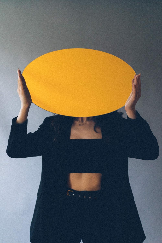 woman in black long sleeve shirt holding yellow balloon