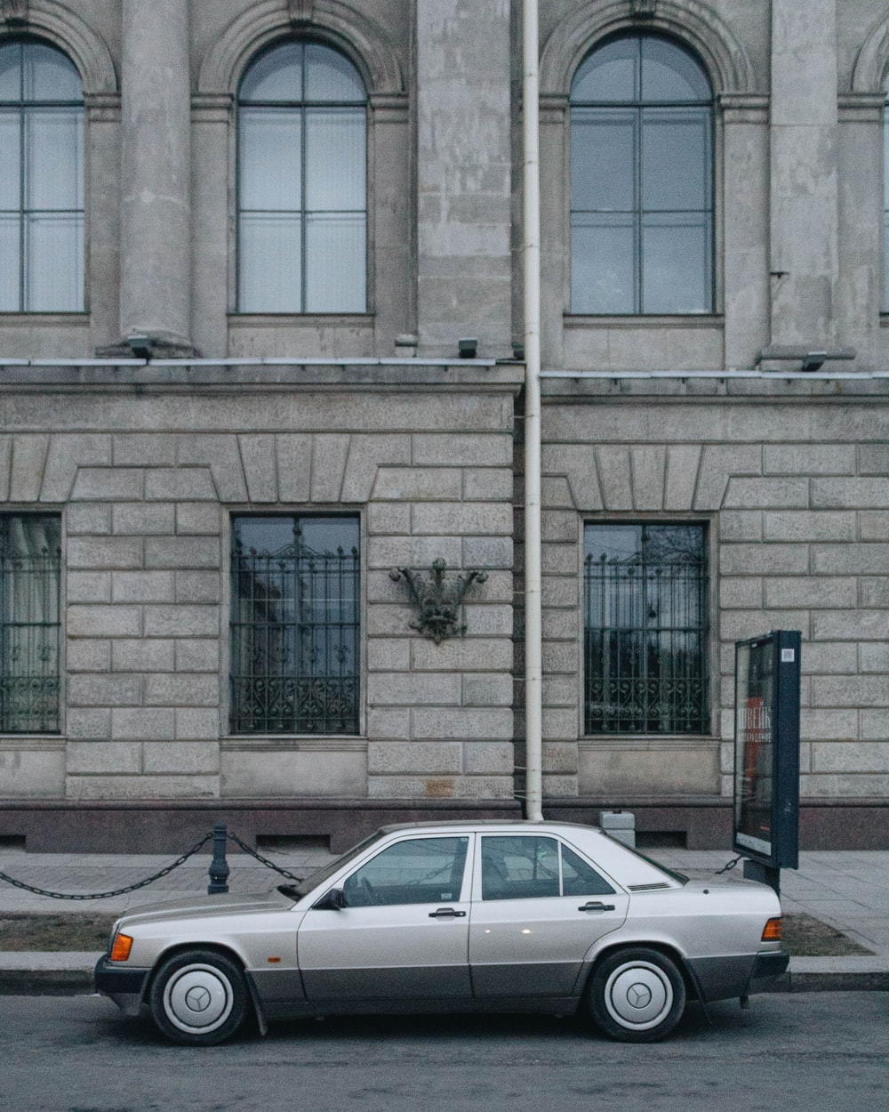 white sedan parked beside building during daytime