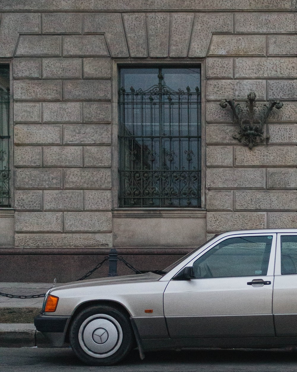white car parked beside brown brick wall