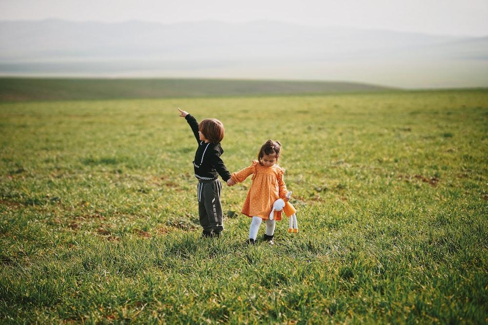 girl in orange dress walking on green grass field during daytime