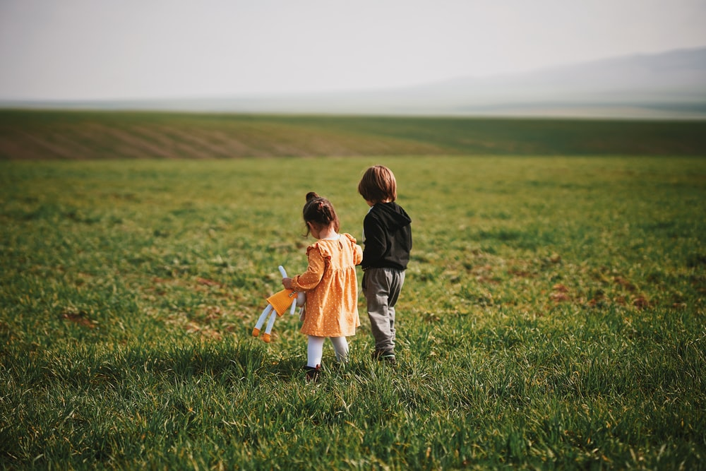 boy and girl walking on green grass field during daytime