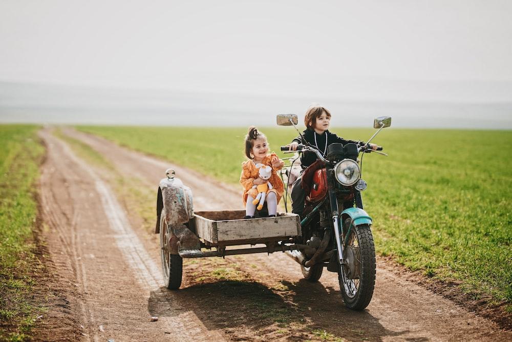 2 boys riding on black motorcycle during daytime