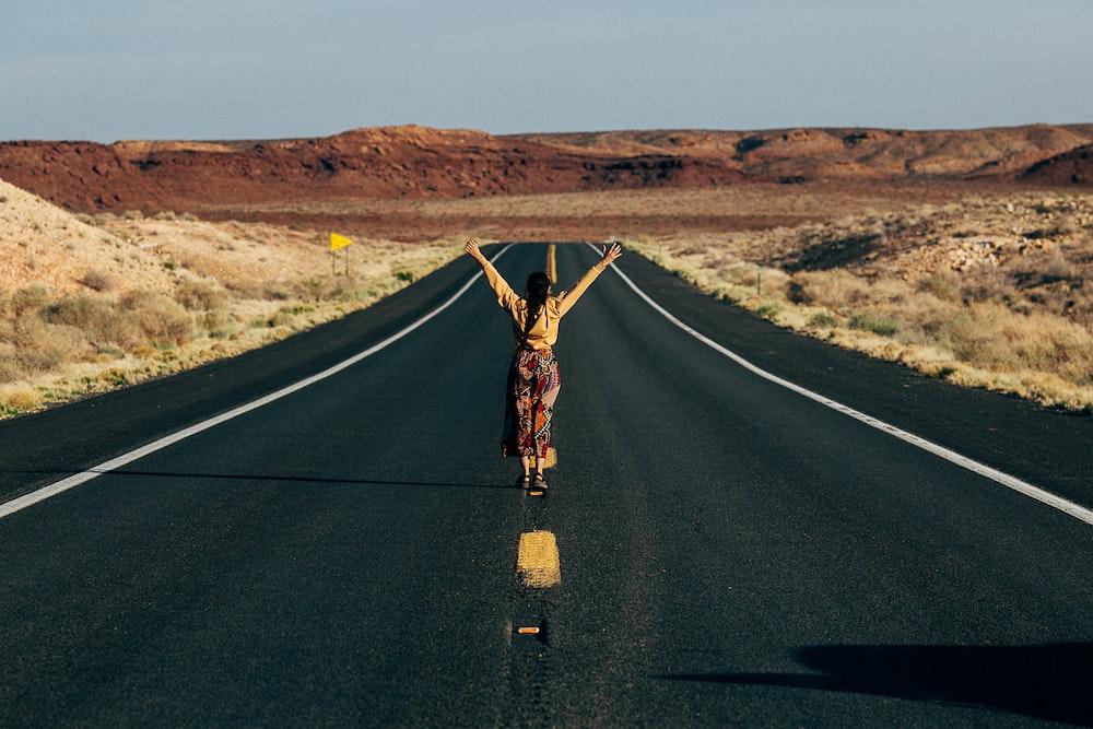 man in black shirt and brown pants standing on black asphalt road during daytime
