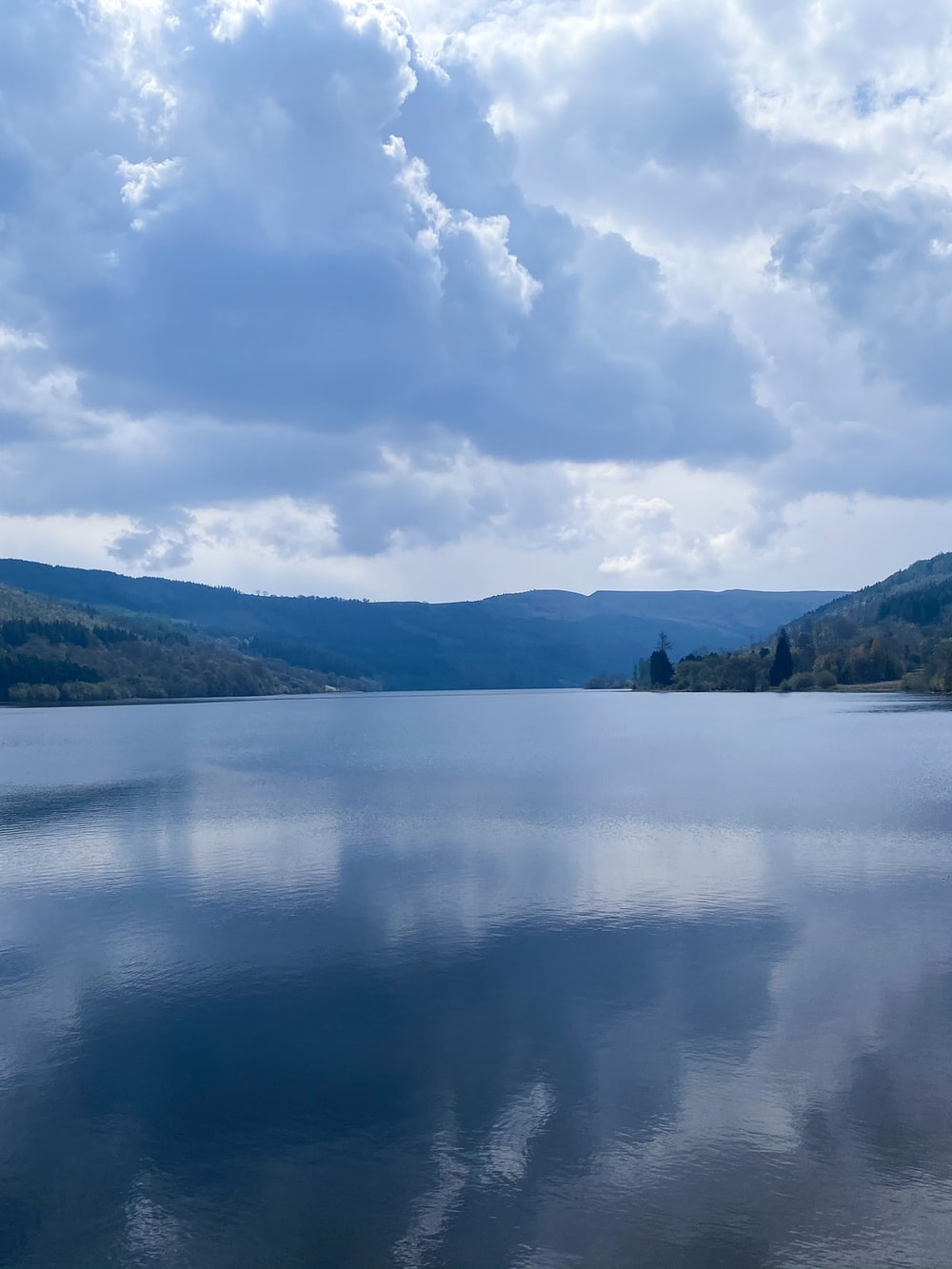body of water near green mountains under white clouds and blue sky during daytime