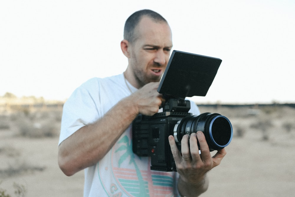 man in white t-shirt holding black camera